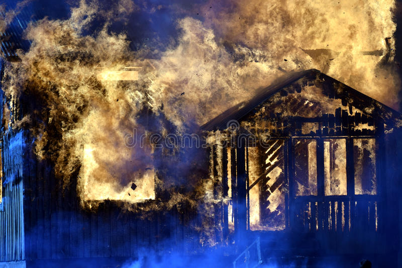 在火焰完全地吞噬的议院 免版税库存图片