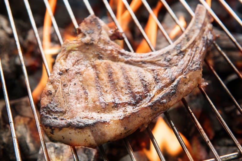 在火焰的烤猪肉牛排在格栅 库存图片