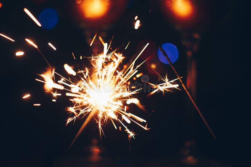 在火焰的闪耀的孟加拉闪烁发光物棍子在与光bokeh的黑背景 圣诞节题材新年背景 节假日 免版税库存图片