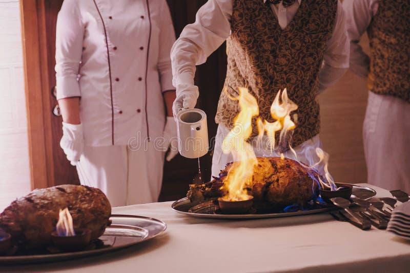 在火的可口肉在结婚宴会在餐馆 烹调与火展示,豪华承办酒席的厨师鲜美膳食 熏制的肉 库存图片