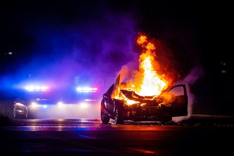 在火的汽车在与警察的晚上在背景中点燃 库存图片