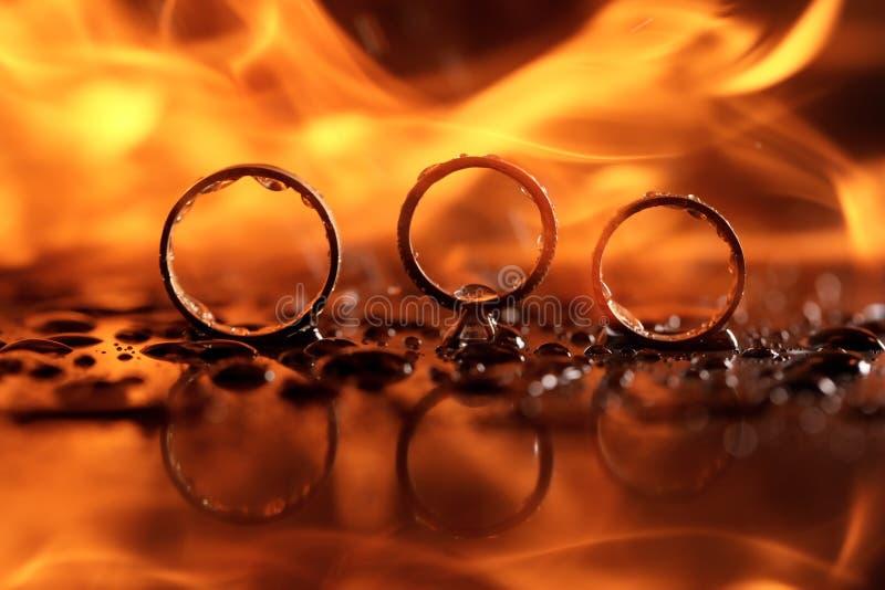 在火的美好的结婚戒指与反射和在水中 免版税库存图片