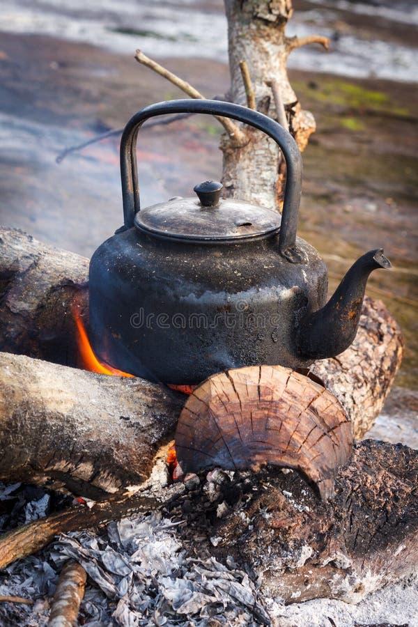 在火的老水壶 免版税库存照片