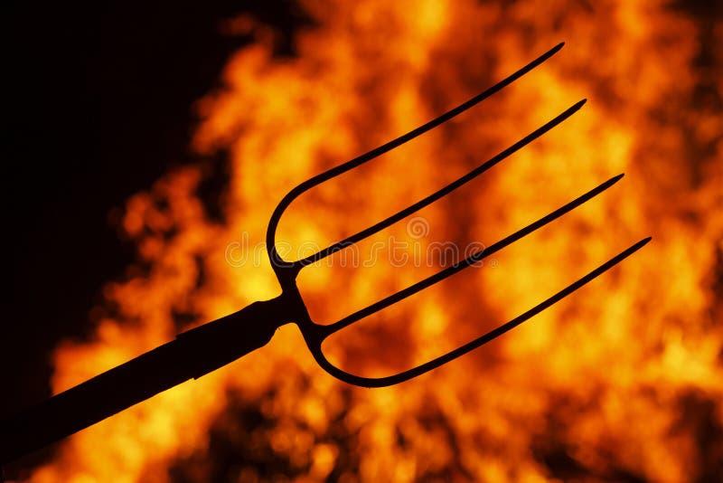 在火背景的地狱叉子  免版税库存照片