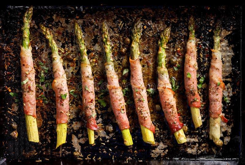 在火腿包裹的烤绿色芦笋增加芳香草本和香料,顶视图 库存图片
