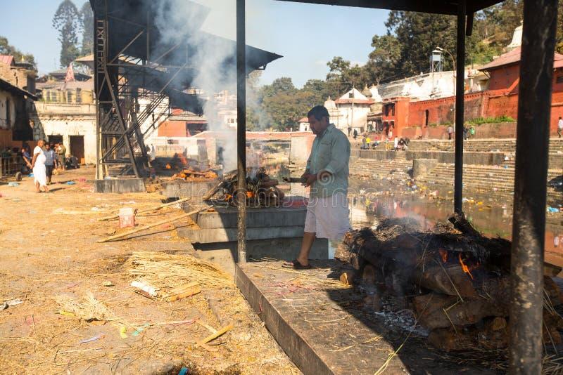 在火葬仪式期间的当地人沿圣洁巴格马蒂河在Pashupatinath寺庙的Bhasmeshvar Ghat在加德满都 免版税库存图片