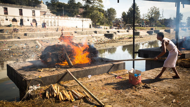 在火葬仪式期间的未认出的当地人沿圣洁巴格马蒂河在Pashupatinath寺庙的Bhasmeshvar Ghat 库存照片