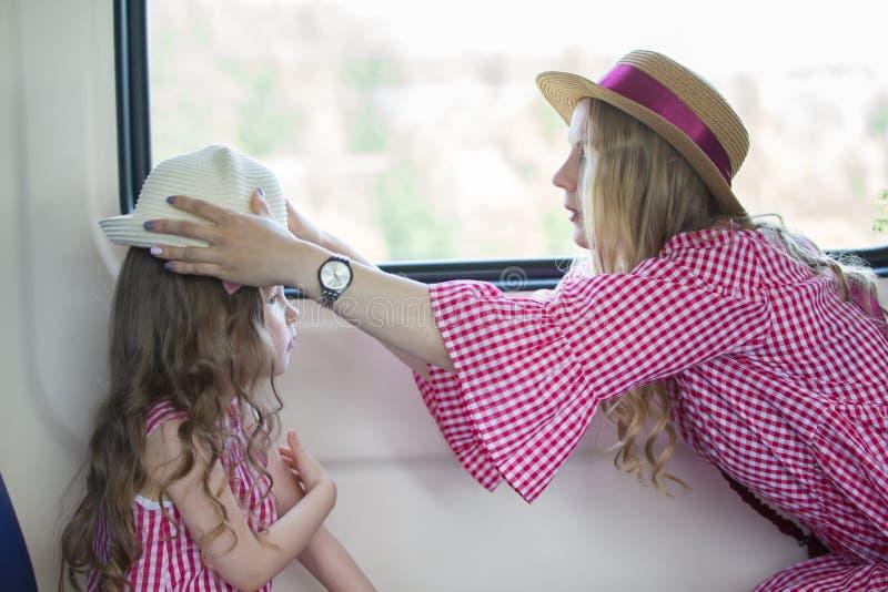 在火车的母亲和女儿旅行-妇女帮助戴女孩的帽子 库存图片