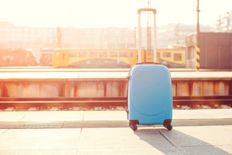 在火车站的手提箱 在平台的旅客手提箱 复制空间 户外蓝色现代行李袋子 旅行和生活方式c 库存照片