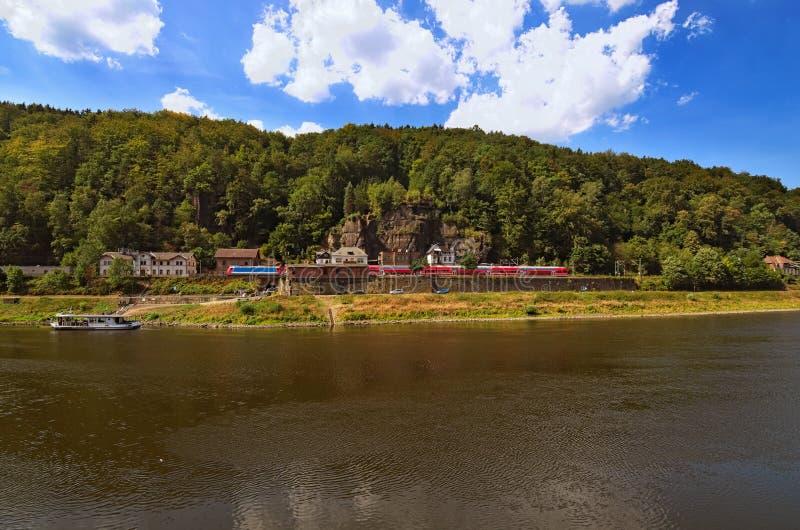 在火车站的红色火车在易北河的易北河的美丽如画的银行 小白色渡轮 库存图片