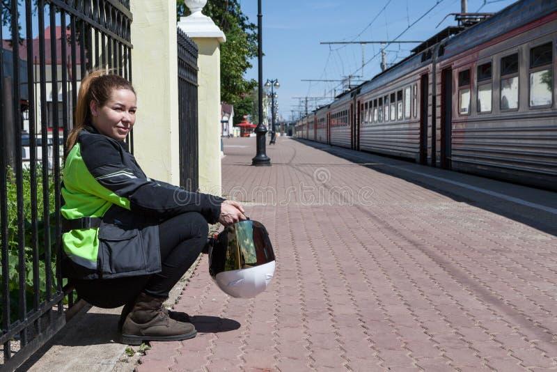 在火车站,在自己的力量下的旅行的妇女摩托车骑士等待的火车在自行车货物发货以后 免版税库存图片