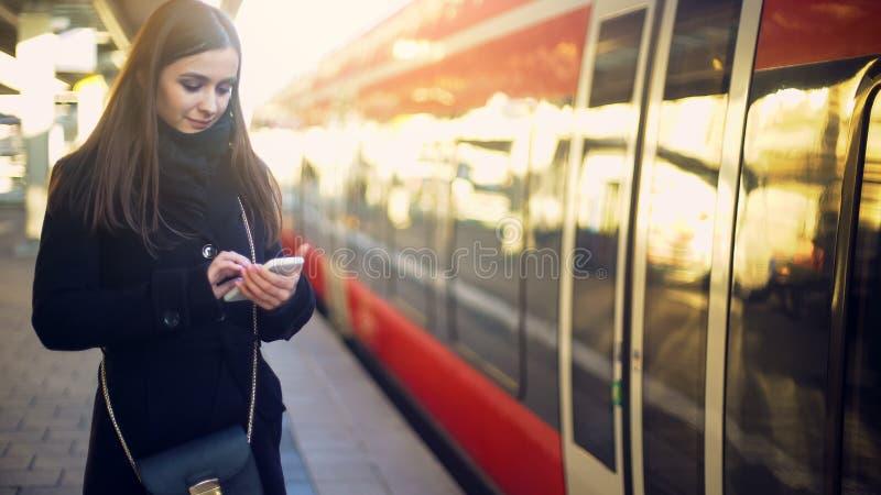 在火车附近的有吸引力的夫人身分和键入在智能手机,网上票 免版税库存照片