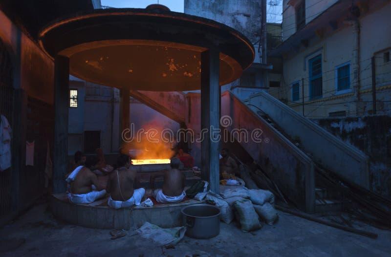在火附近坐的人们在晚上 库存照片