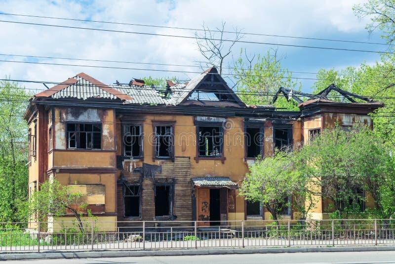 在火以后的二层楼的房子 被毁坏的屋顶 免版税库存照片