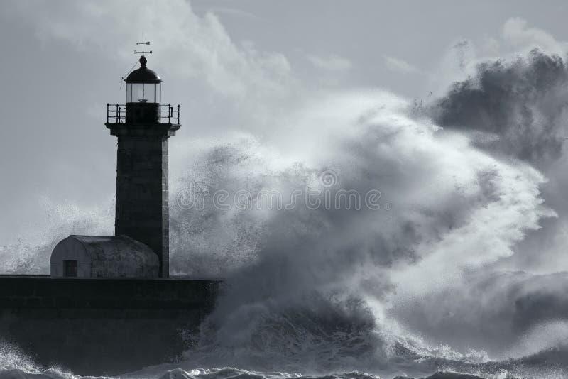 在灯塔的大风雨如磐的波浪 库存图片