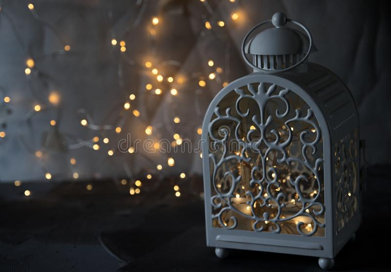 在灯笼、圣诞节闪亮金属片、圣诞节球、闪闪发光和光的蜡烛在背景中 夜光舒适 免版税库存照片