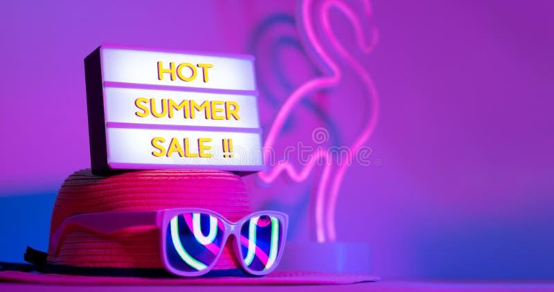 在灯箱的热的夏天销售在有太阳镜便餐火鸟霓虹桃红色和蓝色和绿灯的帽子在与拷贝空间的桌上 库存图片
