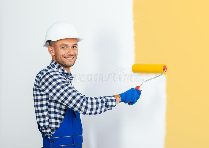 绘在灰棕色的微笑的英俊的画家墙壁 免版税图库摄影