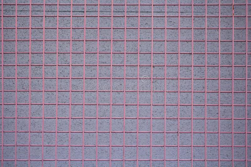 在灰泥墙壁的红色金属栅格 免版税库存照片