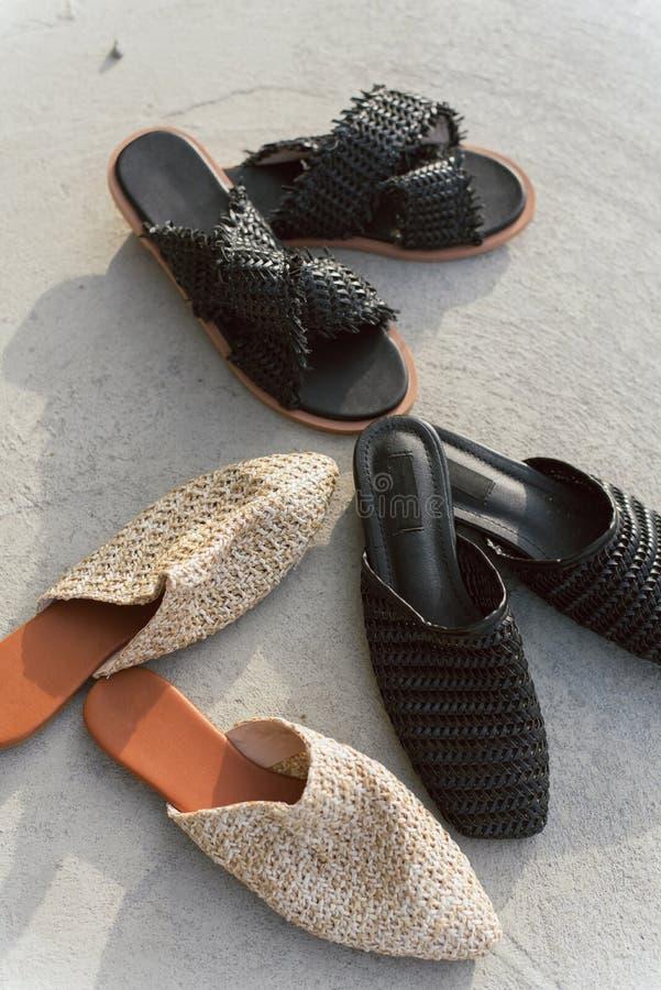在灰色具体背景的许多不同的被编织的鞋子 黑和米黄板岩和骡子 不同时兴和时髦 免版税图库摄影
