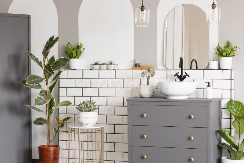 在灰色内阁上的镜子有在明亮的卫生间inte的水盆的 免版税库存照片