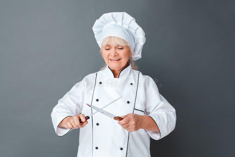 在灰色削尖的刀子的资深妇女厨师演播室身分集中了快乐 免版税库存照片