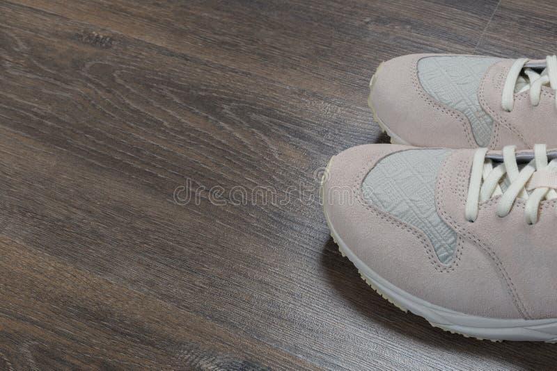 在灰色地板上的运动鞋在家 免版税库存照片