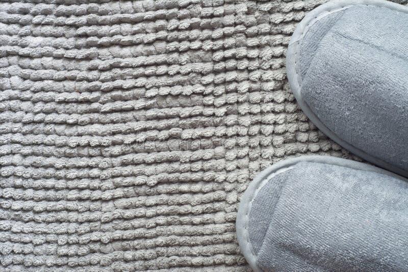 在灰色地毯的拖鞋 库存照片