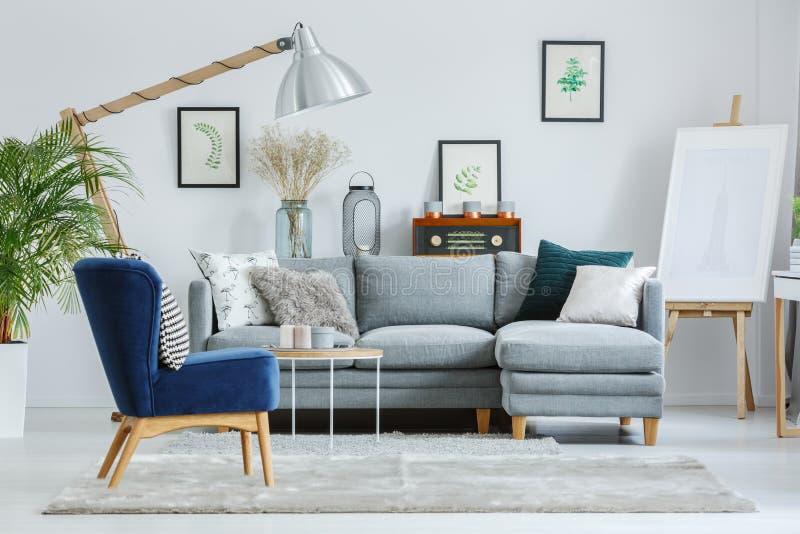 在灰色地毯的蓝色扶手椅子 免版税库存照片