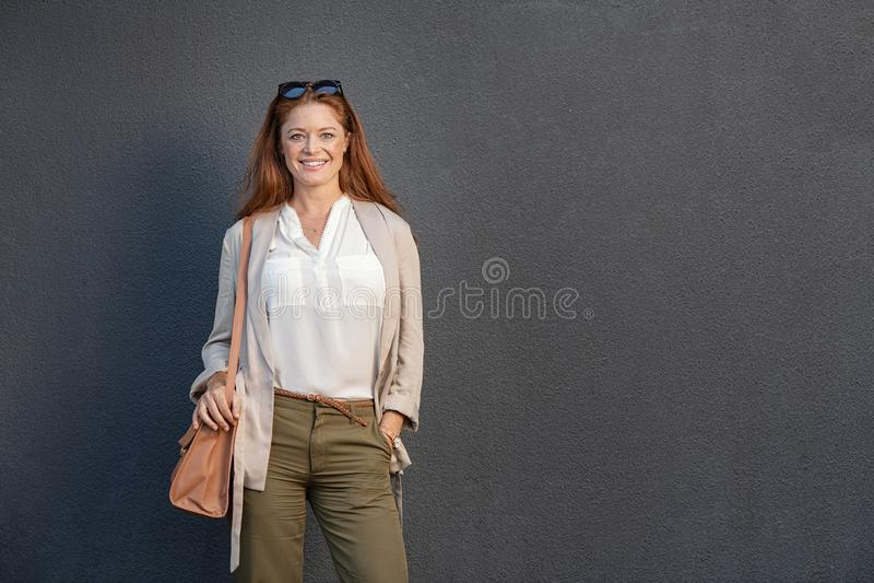 在灰色墙壁上偶然的微笑的妇女隔绝的 免版税库存图片