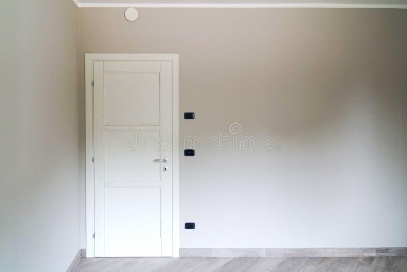 在灰色墙壁上关闭的白色门 库存照片