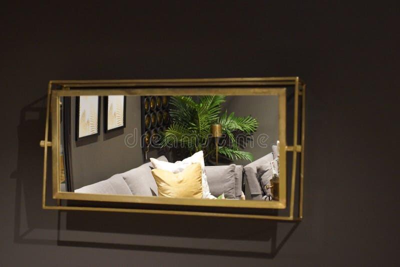 在灰色墙壁上垂悬一个长方形镜子,反射有家具的屋子 免版税库存图片