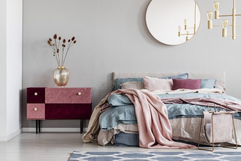 在灰色墙壁上的优等的圆的镜子在时髦的卧室内部与与蓝色,粉红彩笔和米黄卧具和天鹅绒的温暖的床 库存图片