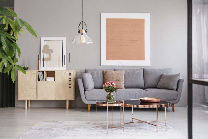 在灰色墙壁上的大绘画在有坐垫的一个典雅的沙发上在有铜家具的一个时髦的客厅 免版税库存图片