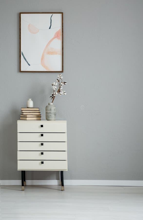 在灰色墙壁上的海报在有书和花的白色内阁上在简单的平的内部 实际照片 免版税库存照片