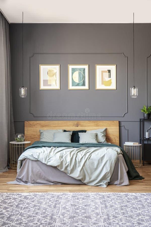 在灰色墙壁上的海报有在木床上的造型的在现代床上 免版税图库摄影