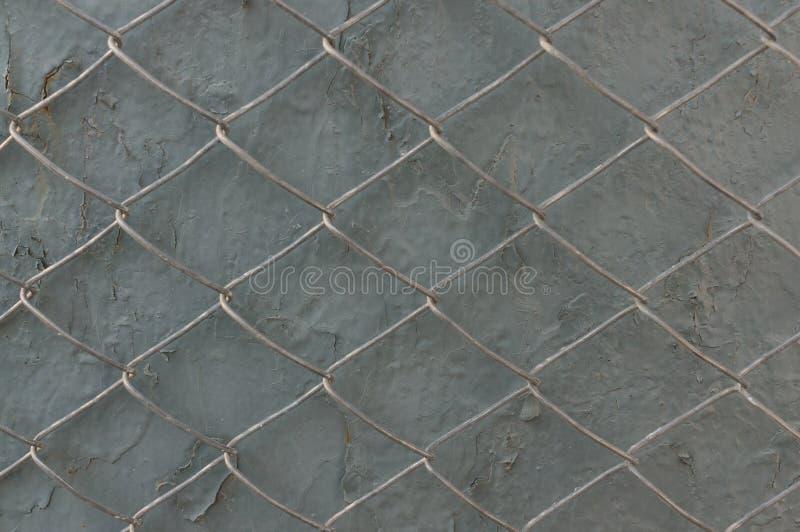 在灰色墙壁上的金属栅格有剥的油漆 E 库存照片