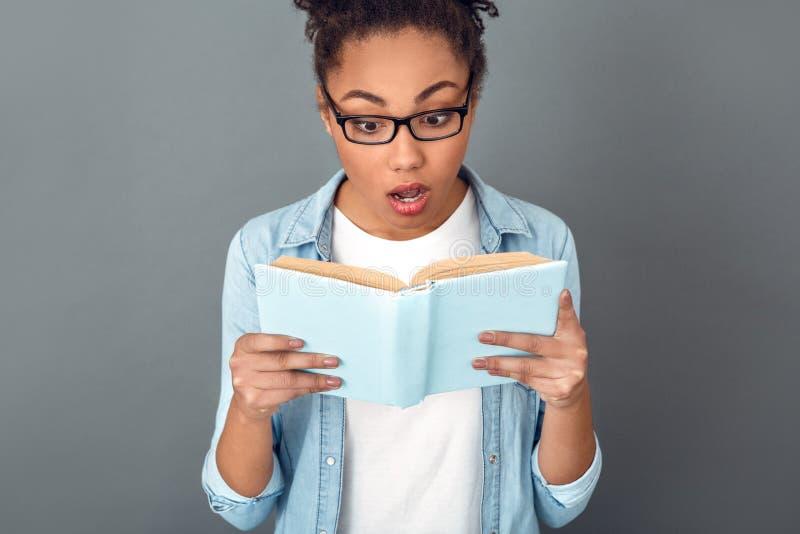 在灰色墙壁演播室偶然每日生活方式学生阅读书特写镜头隔绝的年轻非洲妇女 库存图片