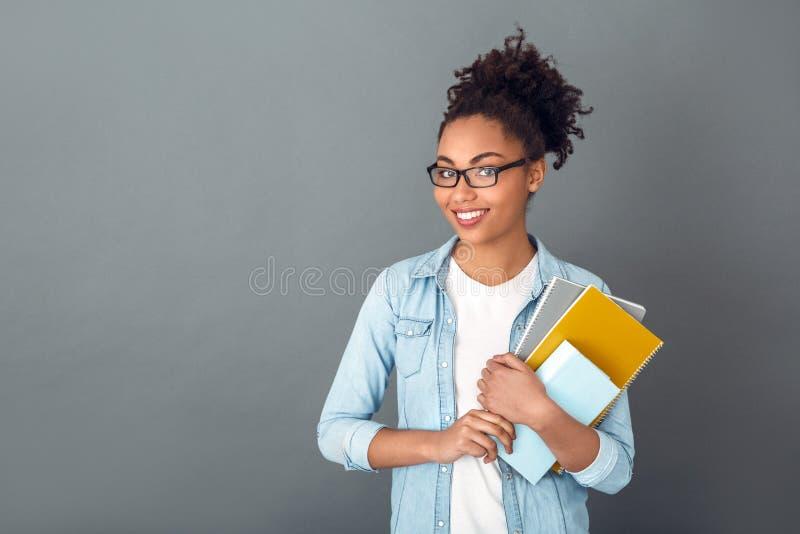 在灰色墙壁演播室偶然每日生活方式学生隔绝的年轻非洲妇女举行笔记本微笑 免版税库存照片