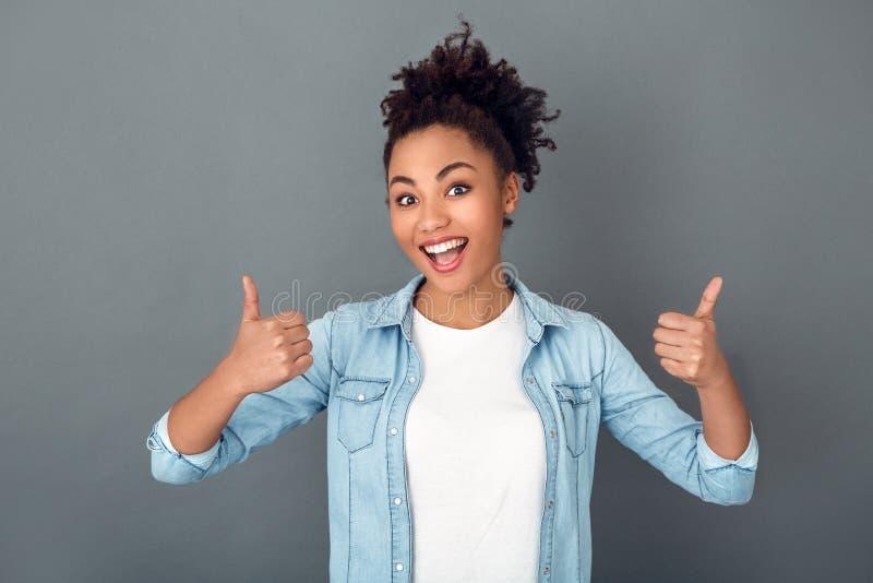 在灰色墙壁演播室偶然每日生活方式赞许隔绝的年轻非洲妇女 库存图片
