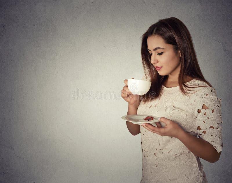 在灰色墙壁背景隔绝的少妇饮用的咖啡 免版税库存照片