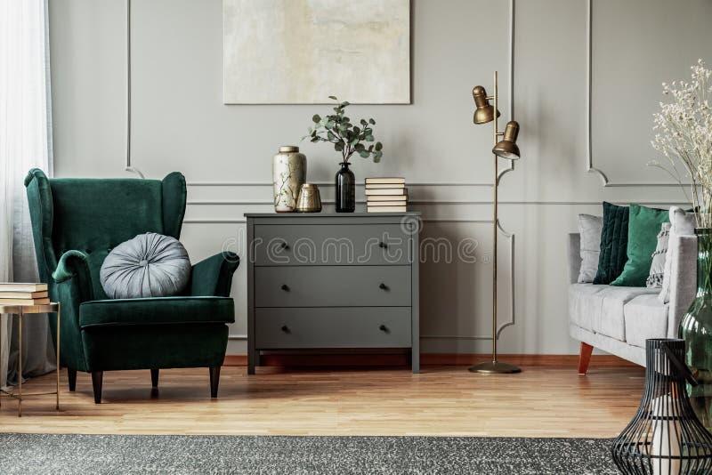 在灰色墙壁o当代客厅内部的抽象绘画与有圆的枕头的,洗脸台鲜绿色扶手椅子和 库存图片
