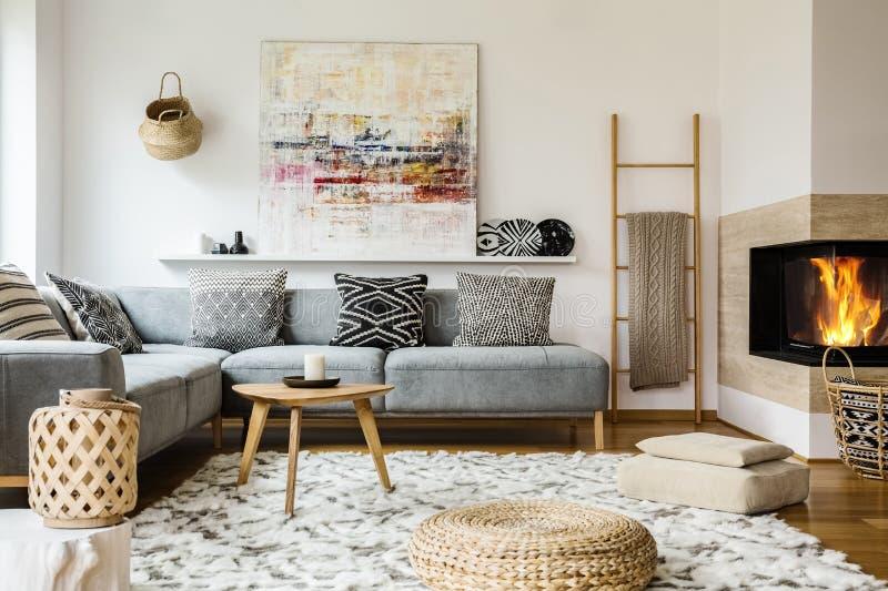 在灰色壁角长椅旁边的木桌在温暖的客厅inte 免版税库存图片