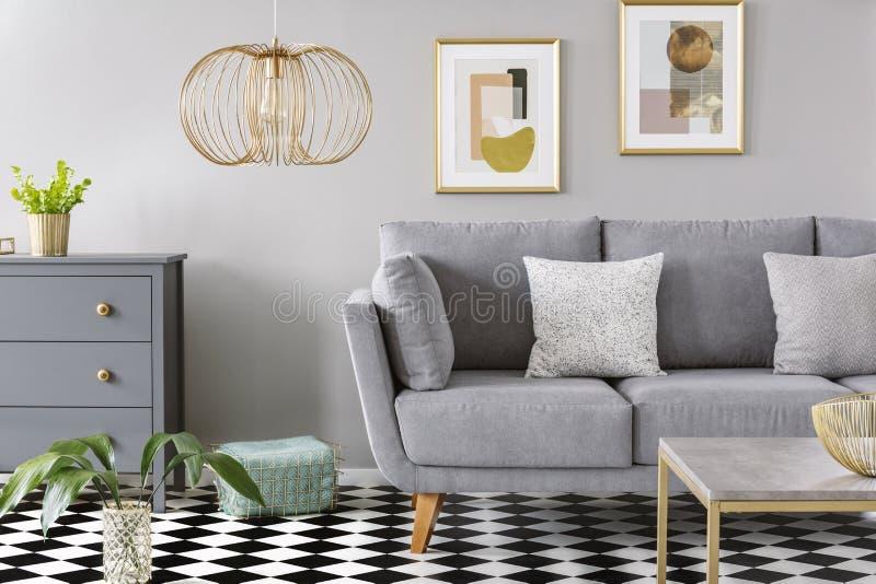 在灰色客厅内部的金灯与在如此灰色上的海报 免版税库存图片