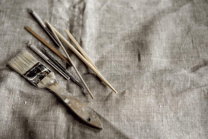 在灰色帆布的黏土工具 掠过,木棍子,堆,金属小铲 免版税库存照片