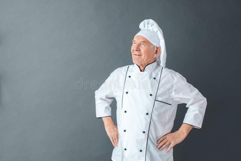 在灰色手上的资深厨师演播室身分在看的臀部在旁边dreamful 免版税库存照片