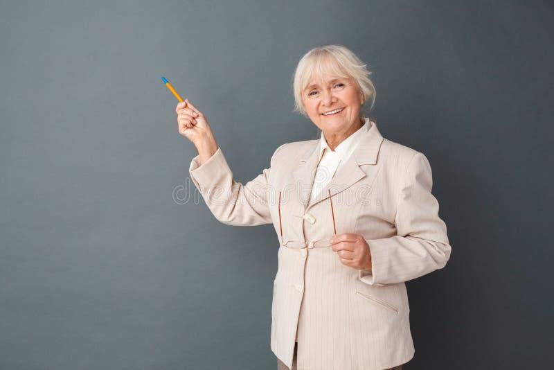 在灰色指向fromal衣服和玻璃演播室身分的资深妇女隔绝的看照相机的墙壁嬉戏 免版税库存图片