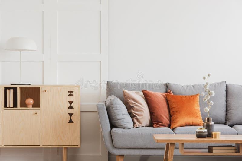 在灰色斯堪的纳维亚沙发旁边的葡萄酒木洗脸台有枕头的 库存照片