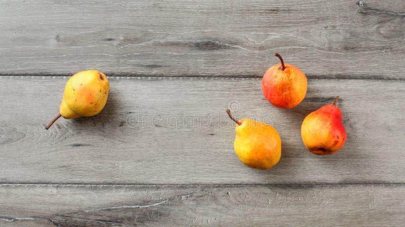 在灰色木书桌安置的四个成熟梨的台式视图 库存照片