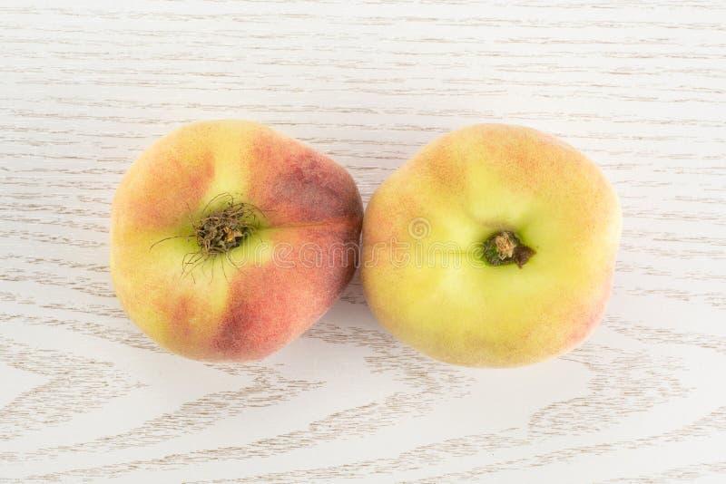 在灰色木头的新鲜的未加工的土星桃子 免版税库存图片